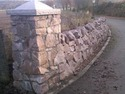Red granite drystone wall; cement/lime pillar; shaped granite cap