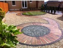 Indian sandstone paving,circles crafted by hand (not circle packs),complimented with coloured aggregates,and turf.
