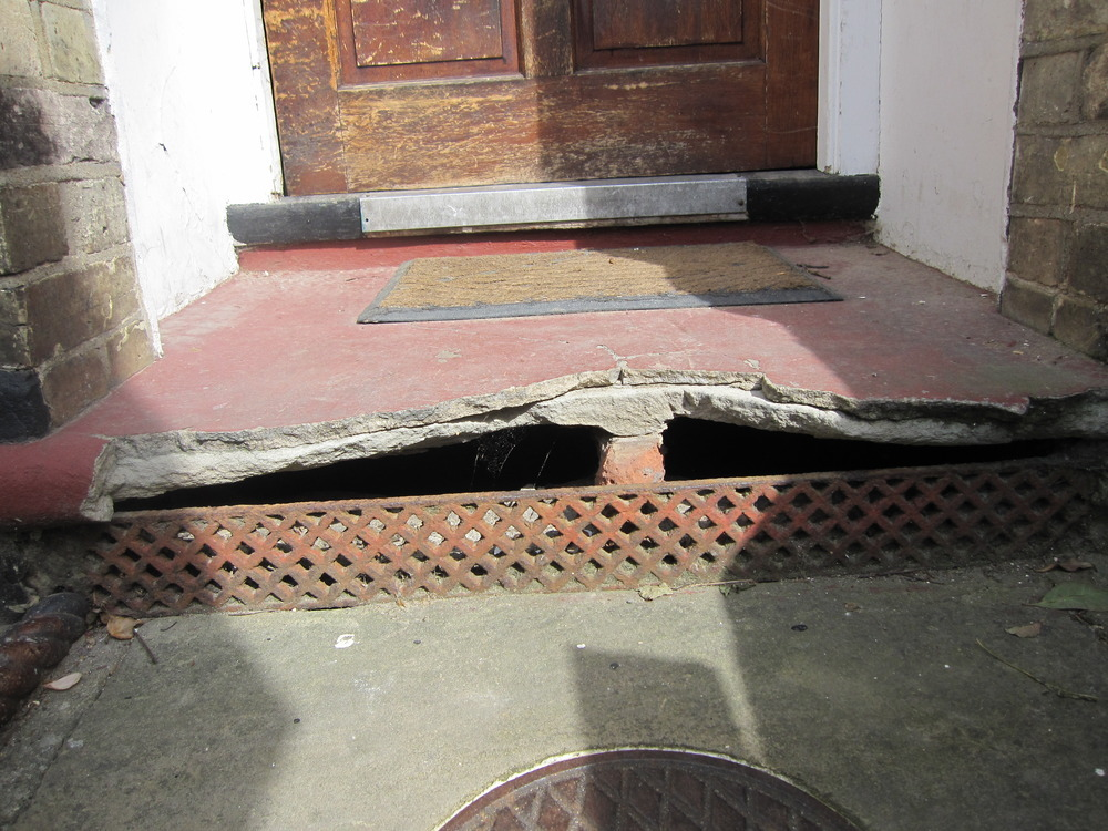 Front Door Step stone doorstep repair & basket of pine cones on a rustic stone